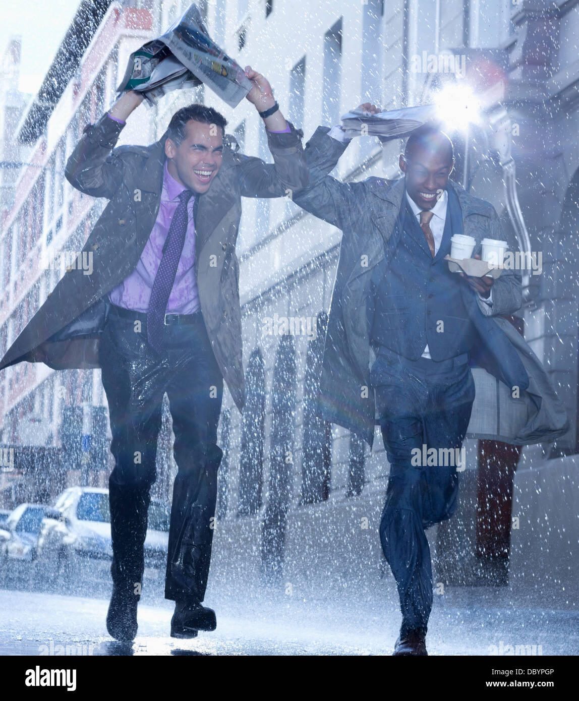 Businessmen carrying coffee and covering heads with newspaper in rain - Stock Image
