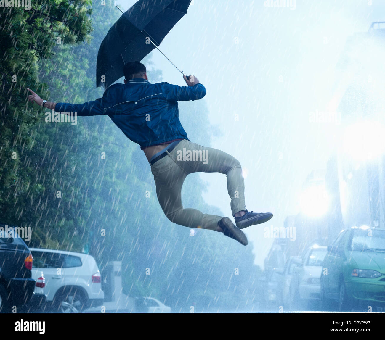 Man with umbrella jumping in rain - Stock Image