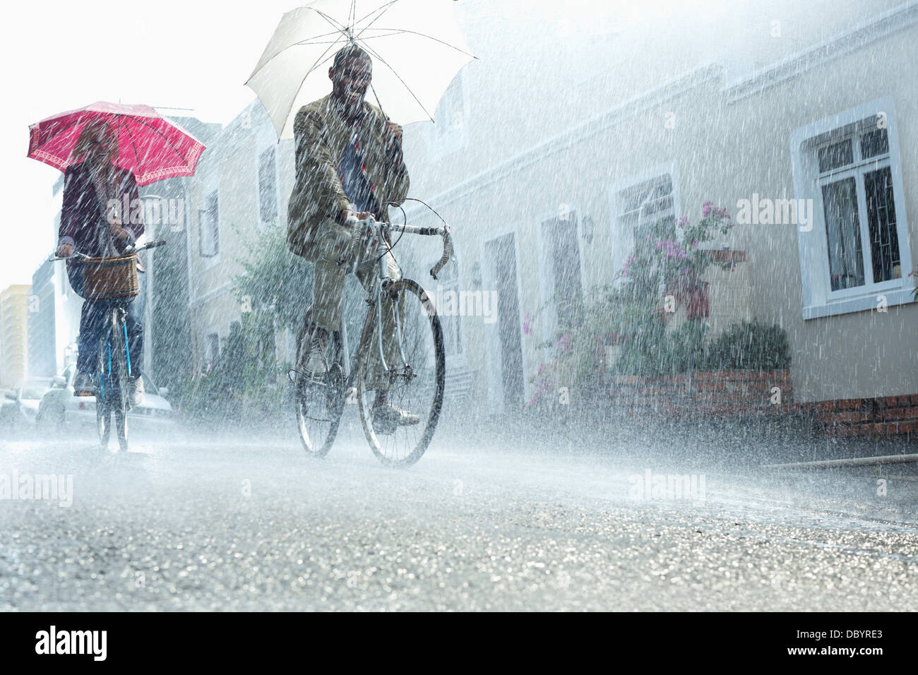 Couple with umbrellas riding bicycles in rain - Stock Image