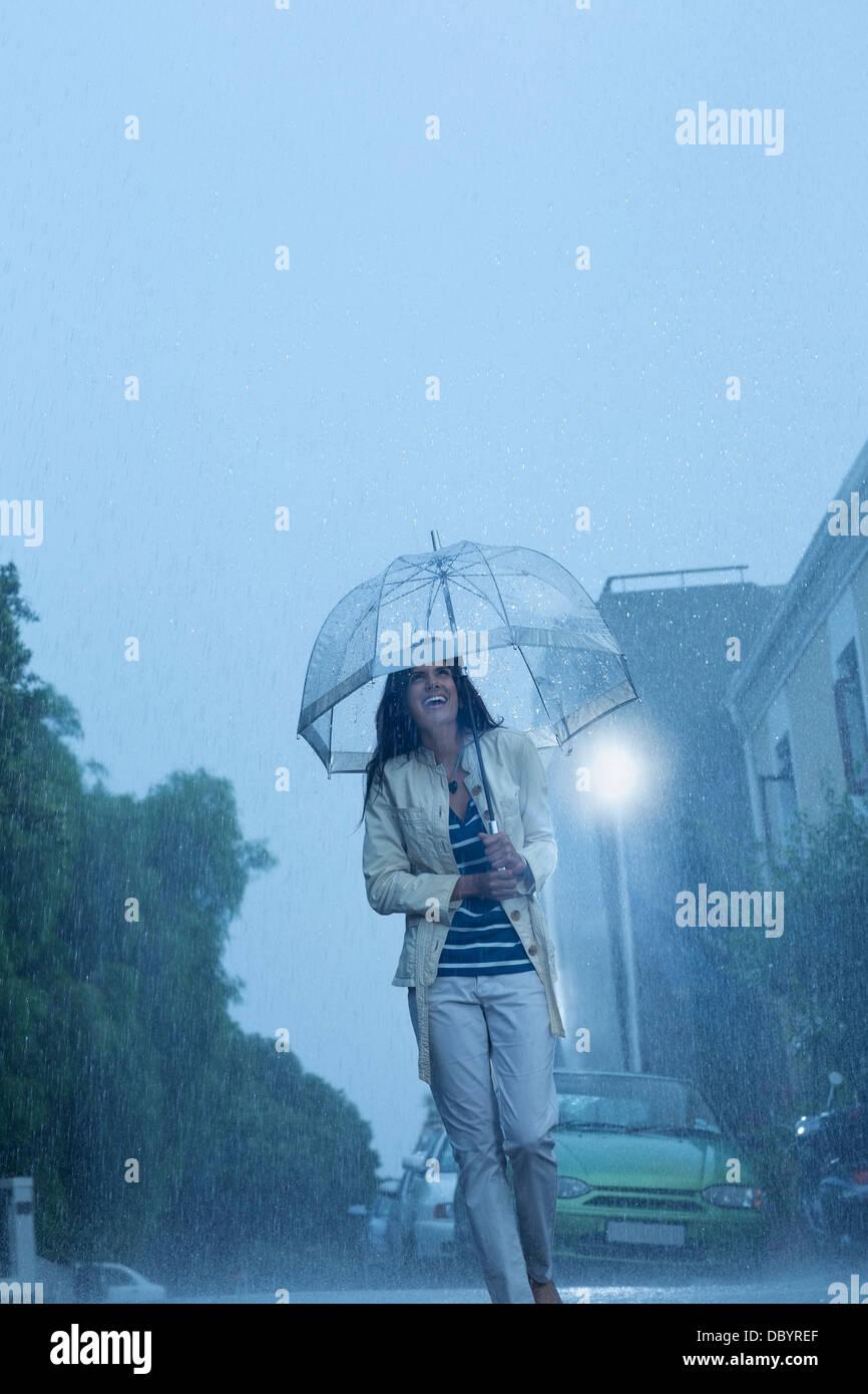 Happy woman with umbrella walking in rain Stock Photo