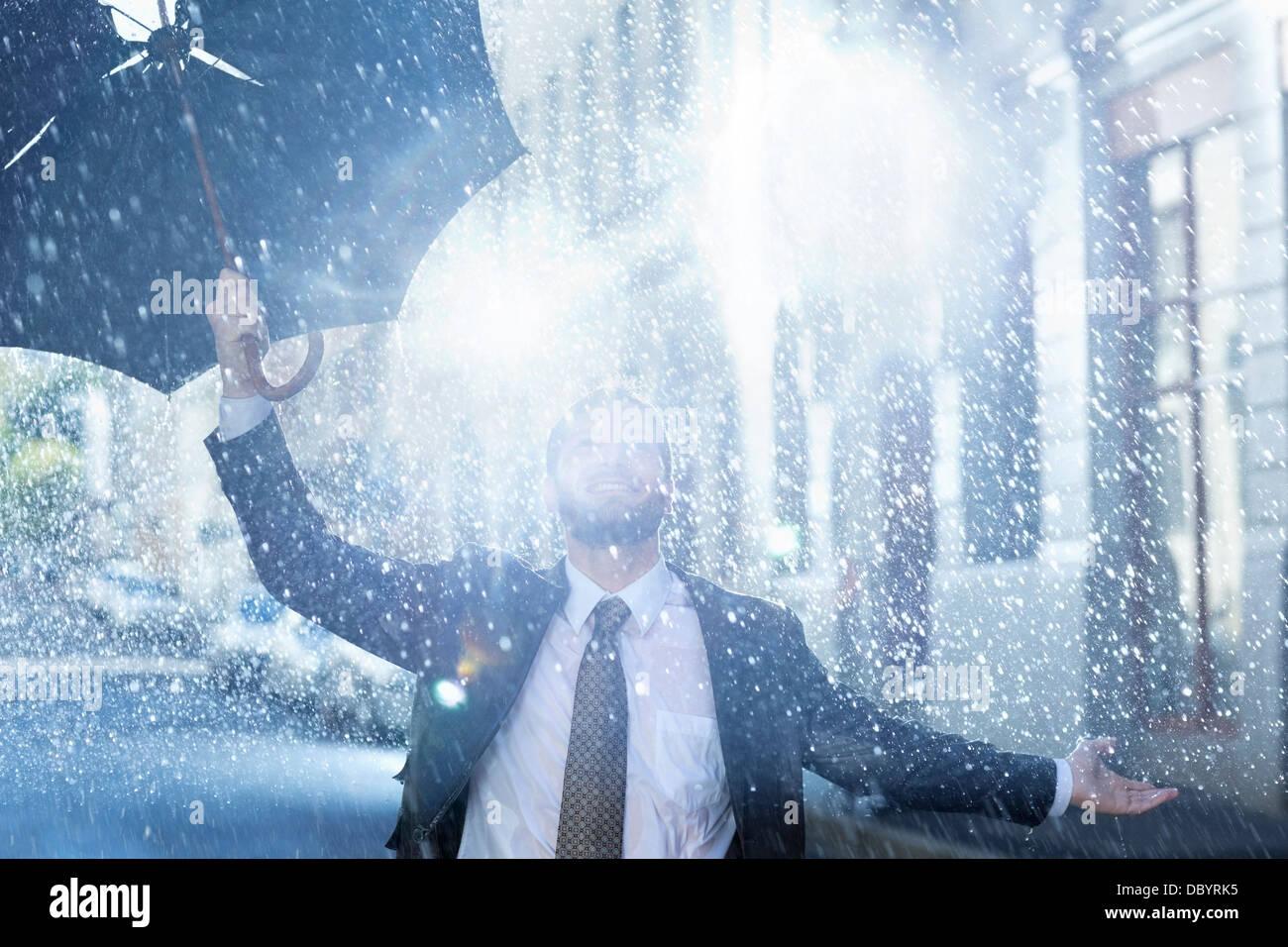 Enthusiastic man with broken umbrella in rain Stock Photo
