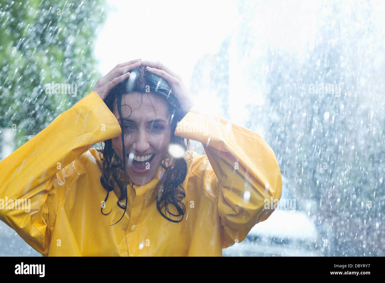 Happy woman with hands on head in rain - Stock Image