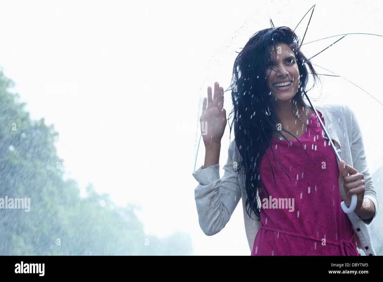 Portrait of smiling woman under umbrella in rain Stock Photo