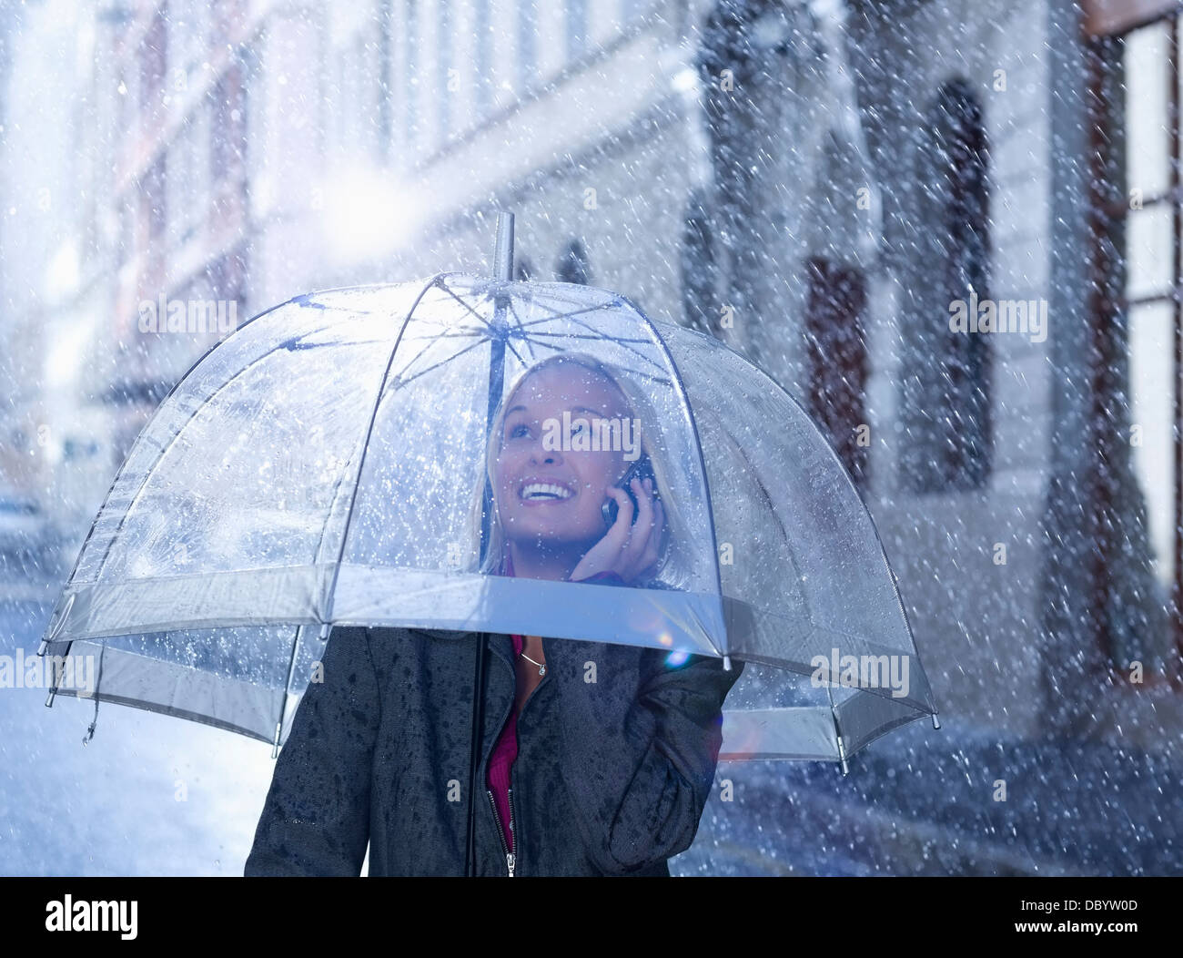 Smiling businesswoman talking on cell phone under umbrella in rainy street Stock Photo