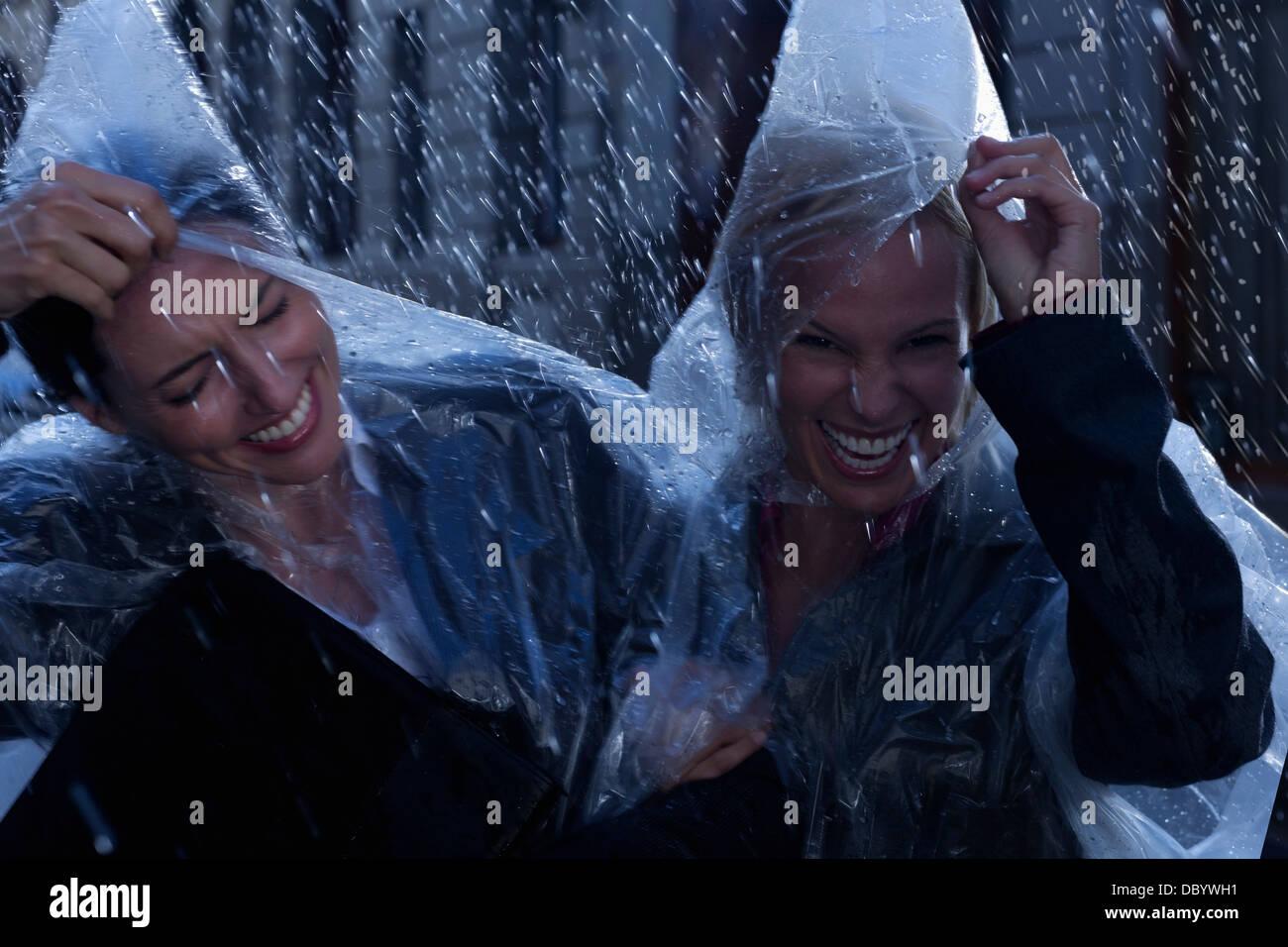 Laughing businesswomen wearing ponchos in rain - Stock Image