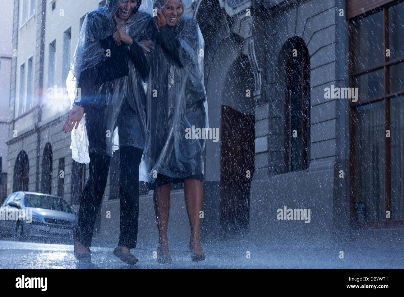 Businesswomen in ponchos walking in rainy street - Stock Image