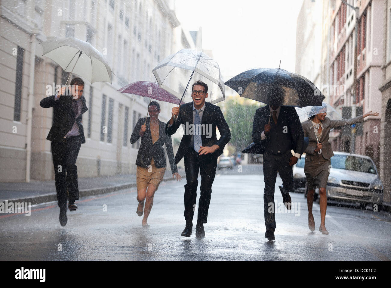 Business people with umbrellas running in rainy street - Stock Image