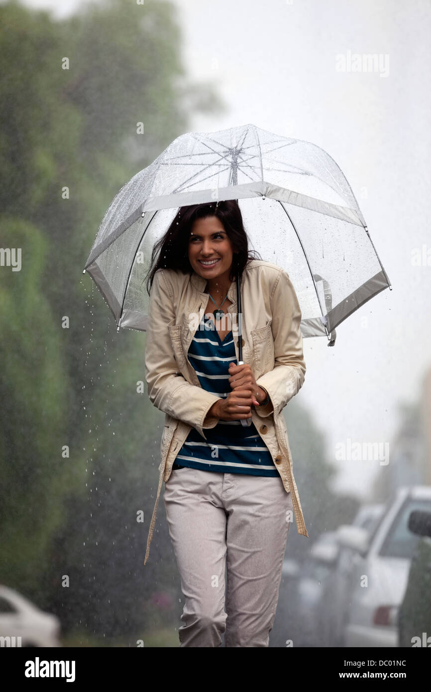 Happy woman under umbrella in rain Stock Photo