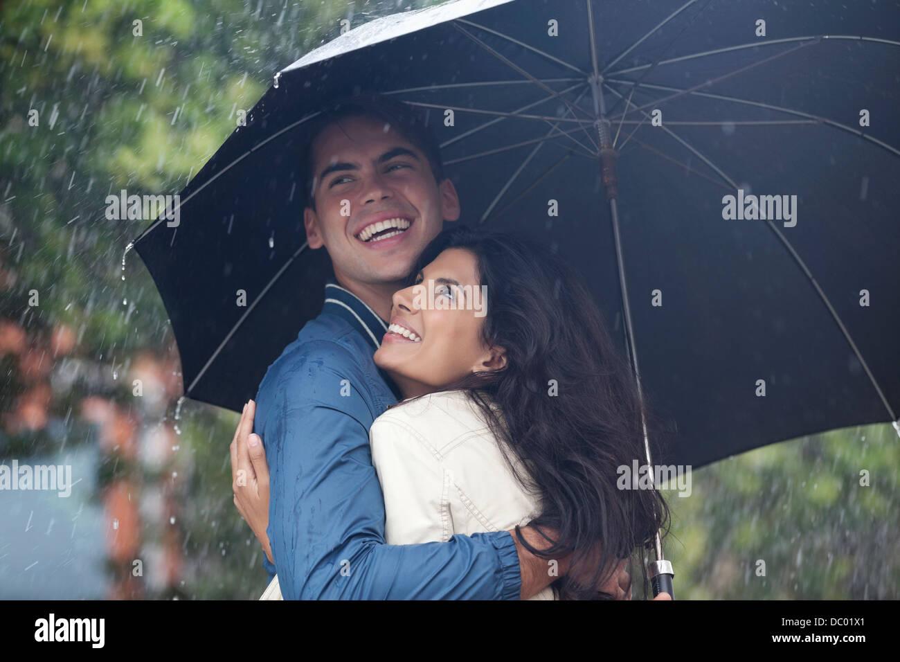 Happy couple hugging under umbrella in rain stock image