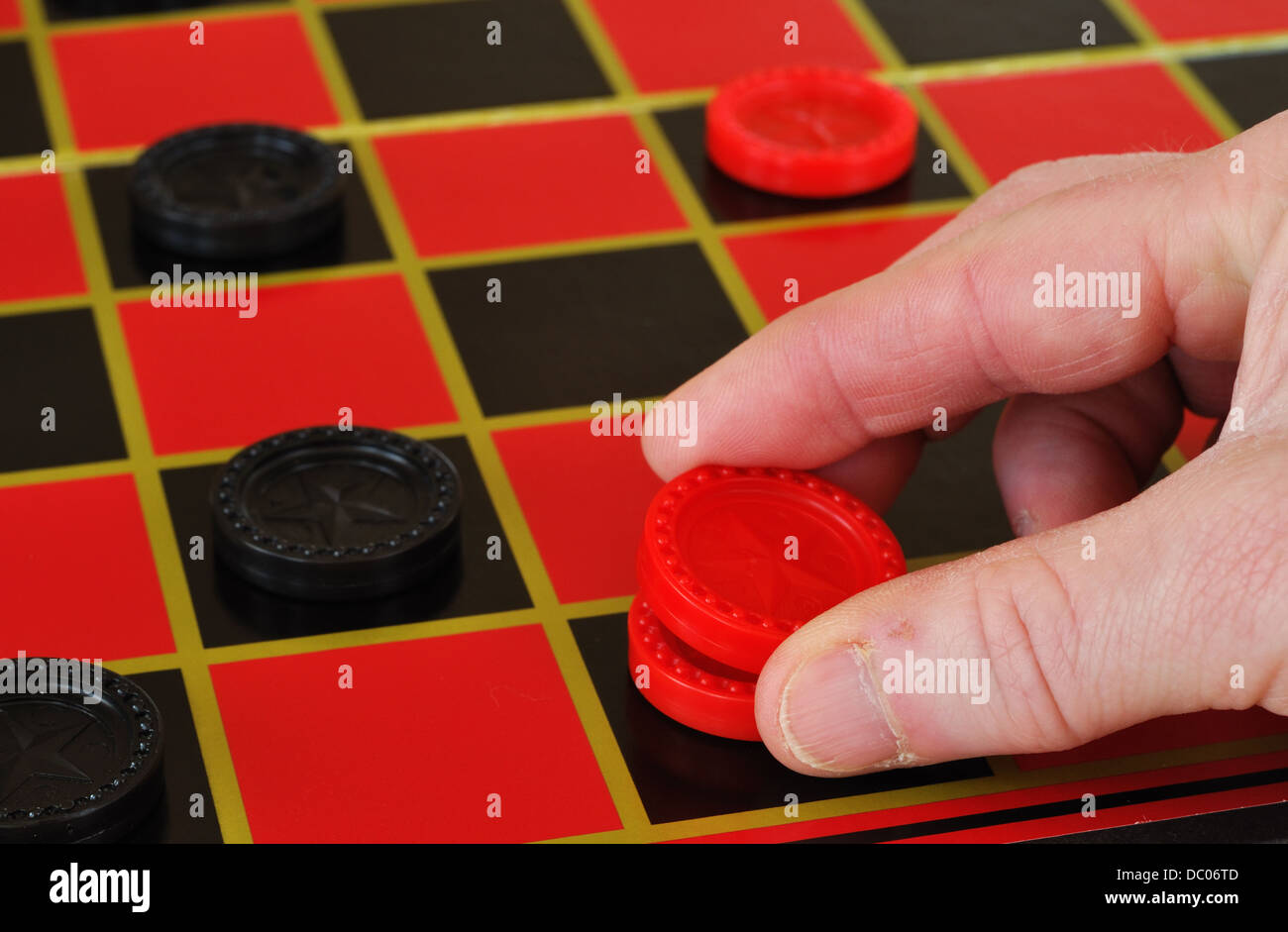 Playing draughts / checkers game on a checker board - Stock Image