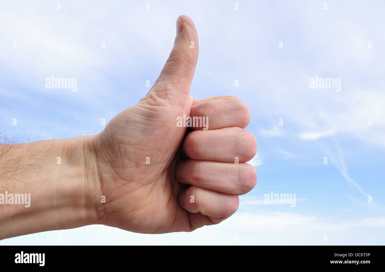 Male hand making humbs up sign outdoors - Stock Image