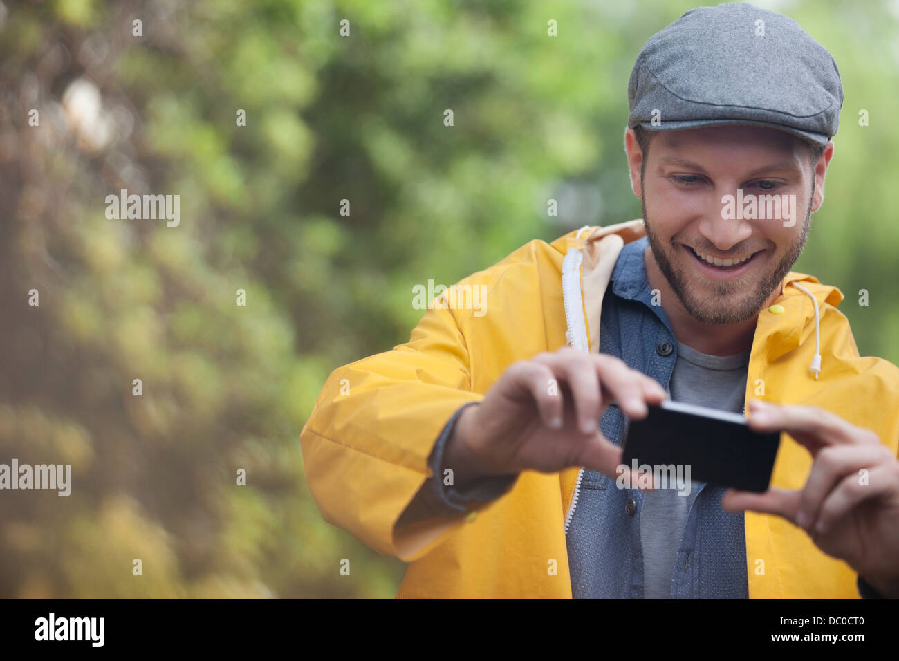 Happy man taking photograph with camera phone - Stock Image