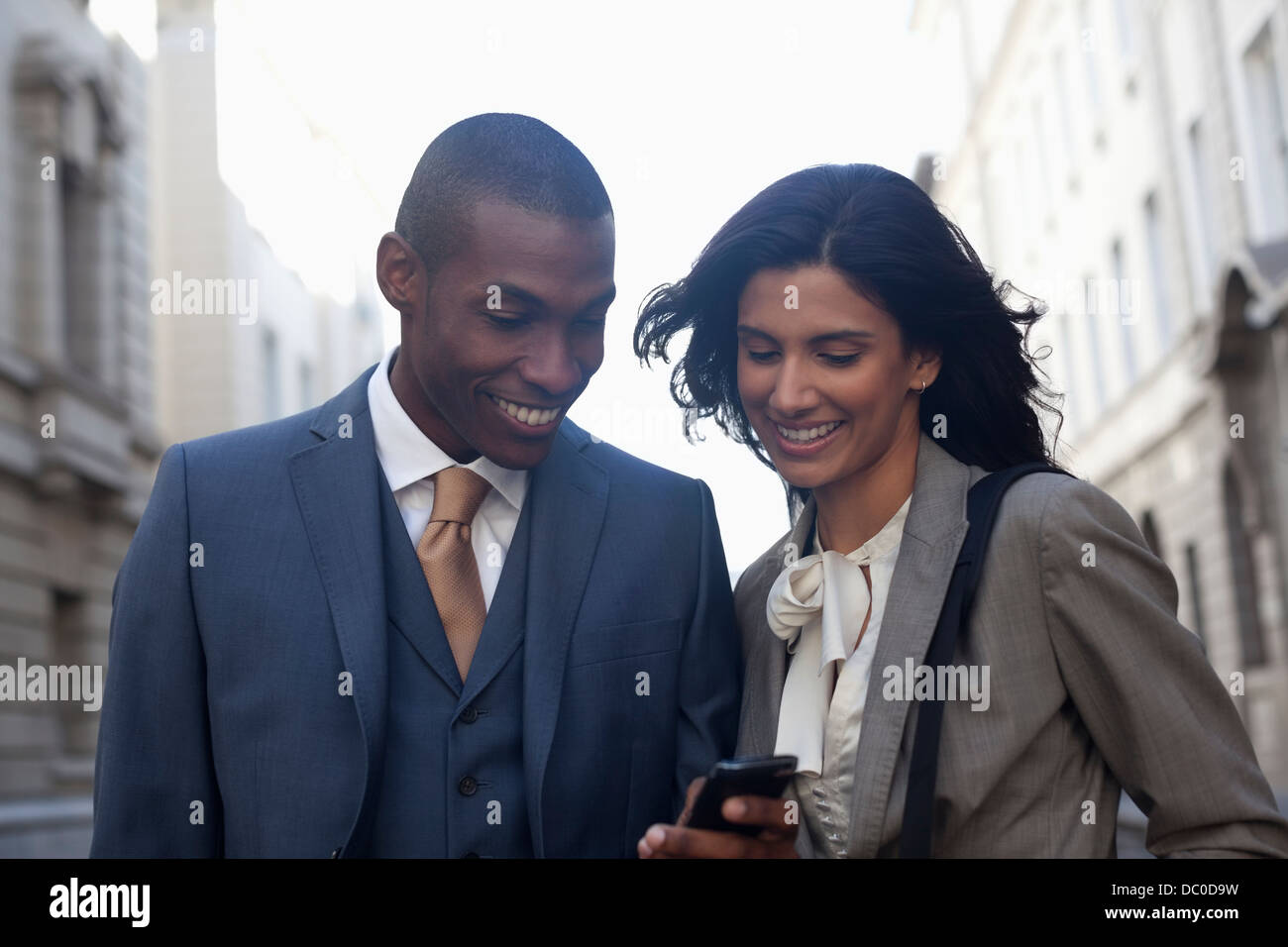 Smiling business people text messaging with cell phone - Stock Image