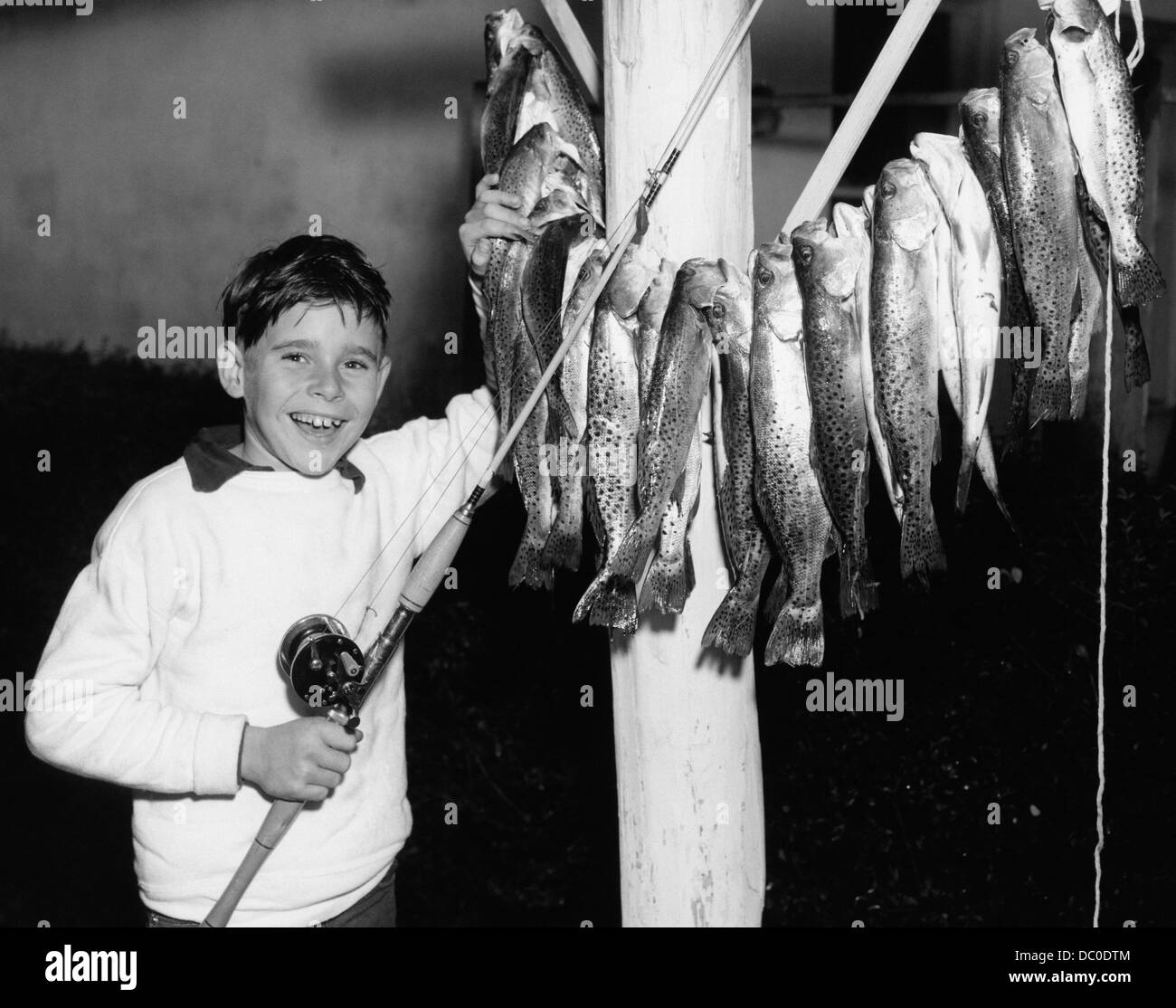 1950s SMILING BOY PROUDLY DISPLAYING HIS FISH CATCH LOOKING AT CAMERA - Stock Image