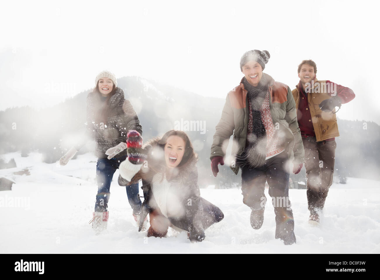 Portrait of friends playing in snowy field - Stock Image