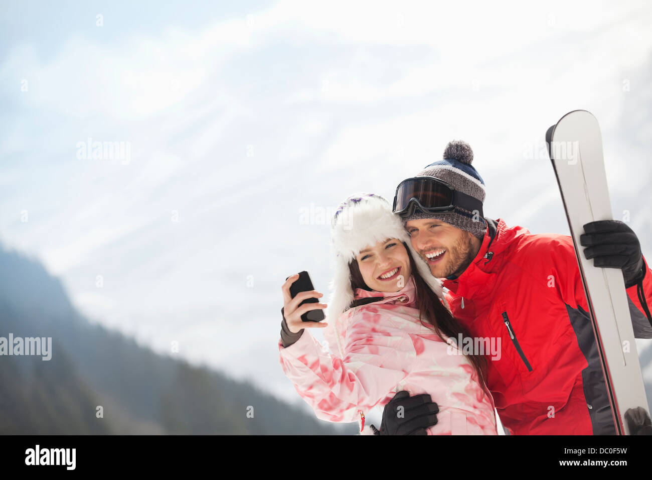 Happy couple with skis taking self-portrait with camera phone - Stock Image