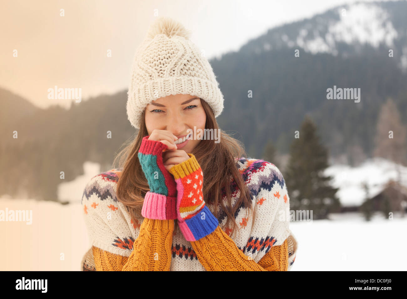 Portrait of smiling woman wearing knit hat in snowy field - Stock Image