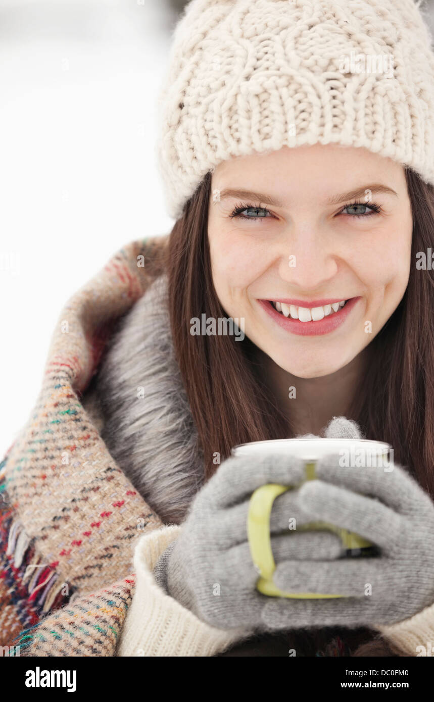 Close up portrait of woman in knit hat and gloves drinking coffee - Stock Image