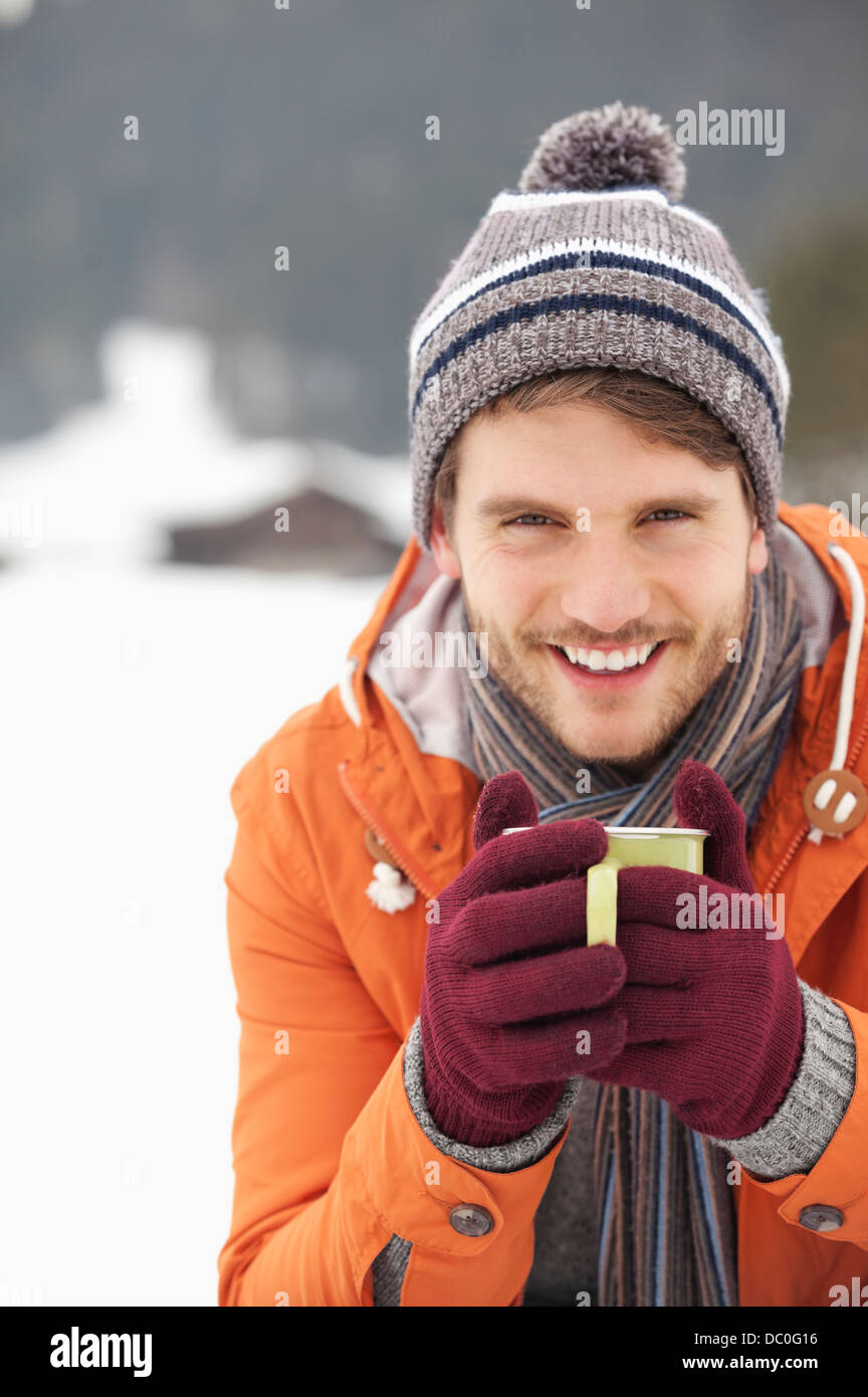 Close up portrait of smiling man in knit hat and gloves drinking coffee in snowy field - Stock Image