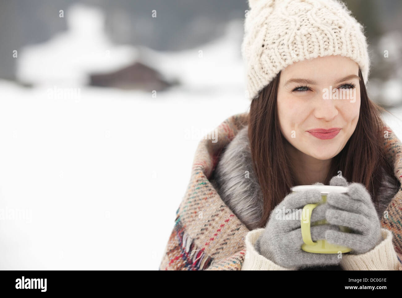 Close up of smiling woman in knit hat and gloves drinking coffee in snowy field - Stock Image