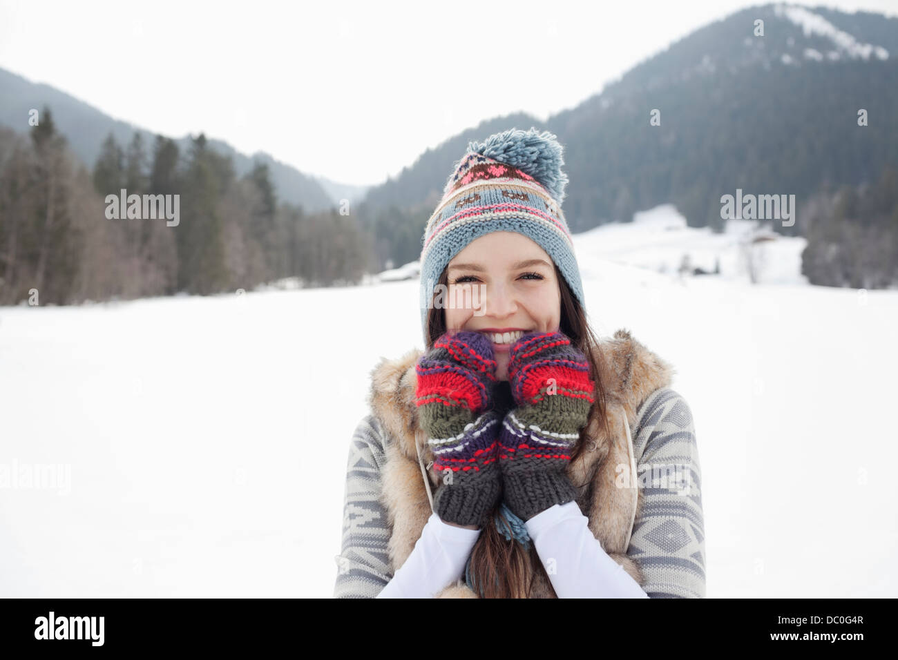 Portrait of enthusiastic woman wearing knit hat and gloves in snowy field - Stock Image