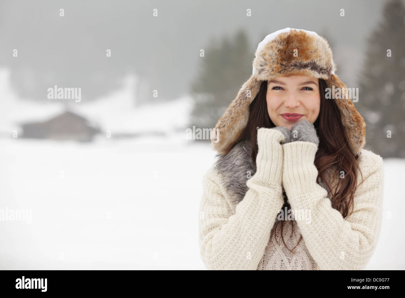 b449778c82251 Portrait of smiling woman wearing fur hat and gloves in snowy field - Stock  Image