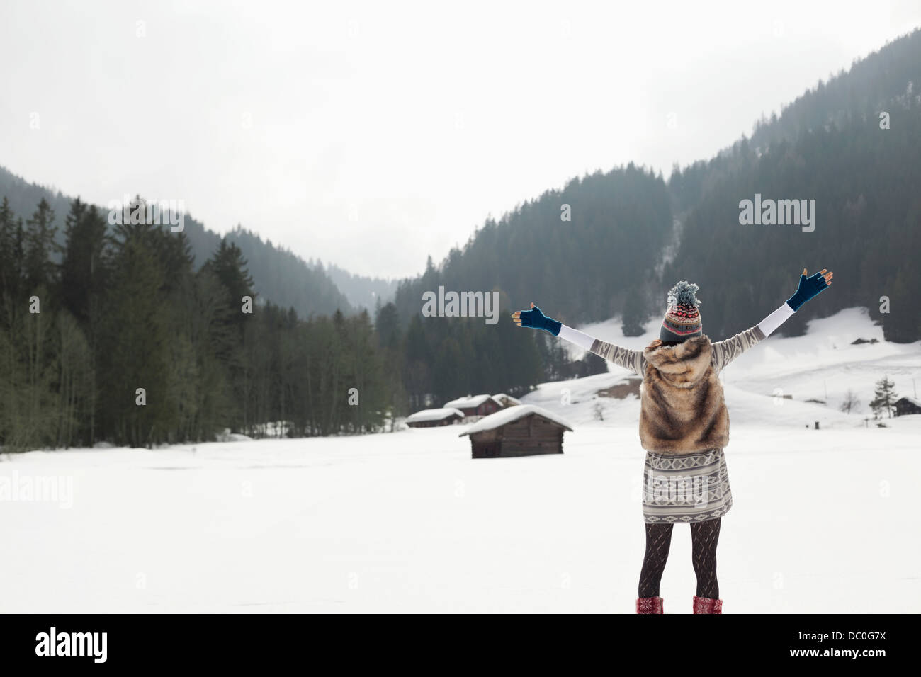 Carefree woman with arms outstretched in snowy field Stock Photo
