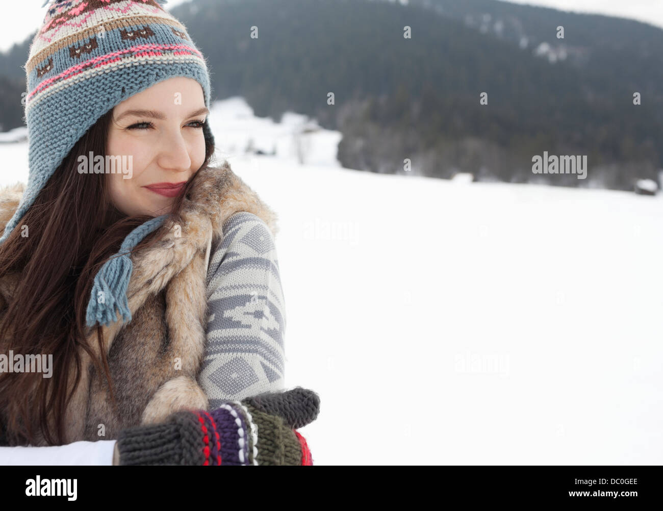 Happy woman wearing knit hat and gloves in snowy field - Stock Image