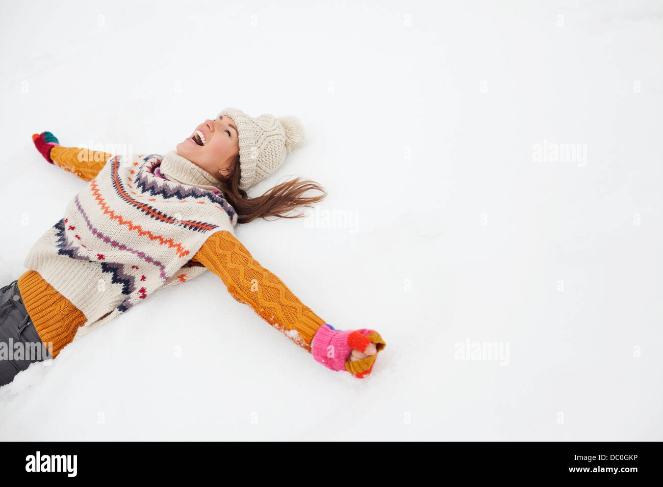 Enthusiastic woman making snow angel Stock Photo