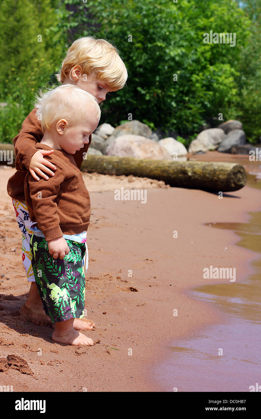a child is hugging and protecting his baby brother as they stand on the beach near the shore of a lake, watching - Stock Image