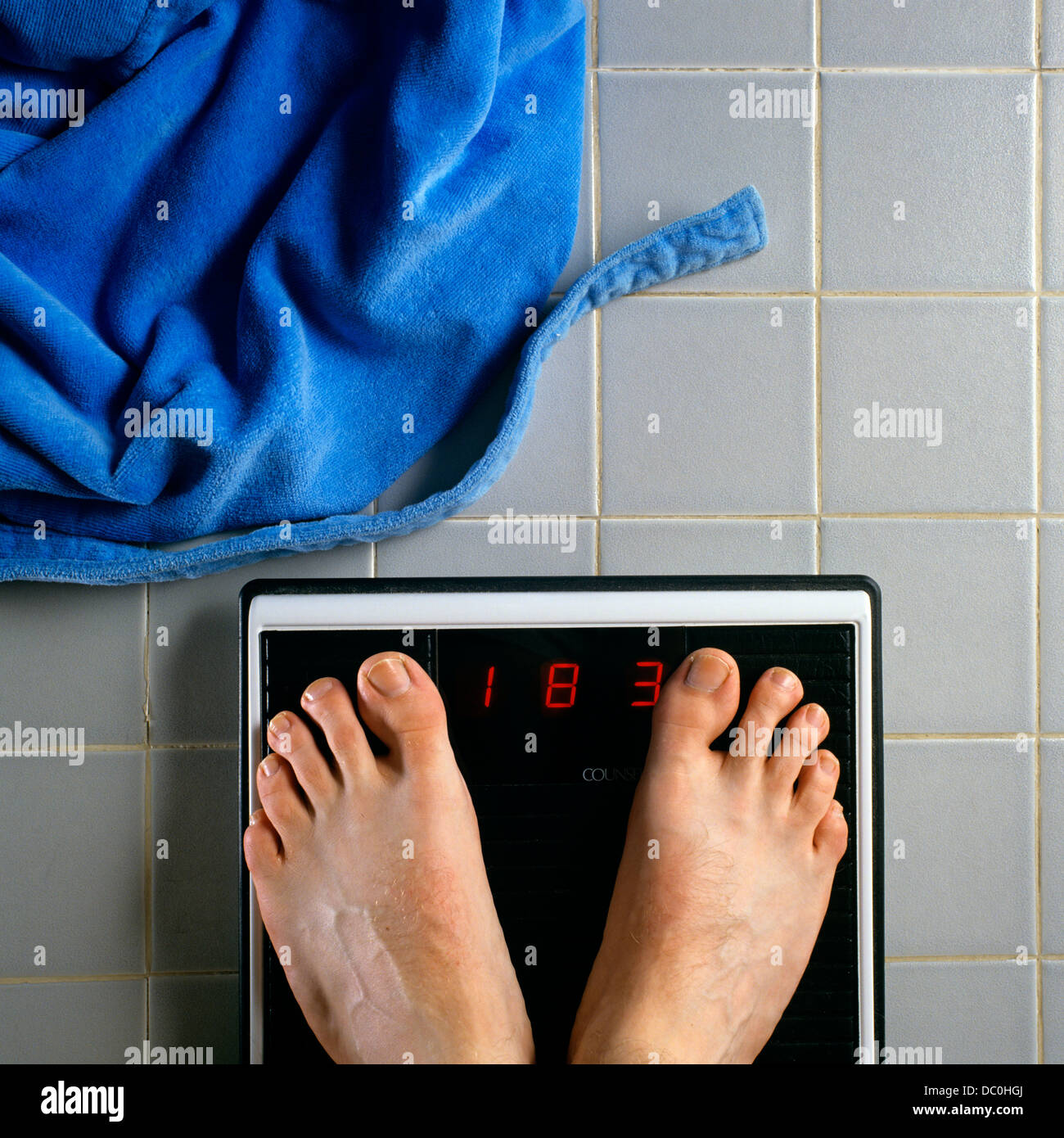 1990s Male Feet On Bathroom Scale Weight Of 183 Pounds Blue Terry Robe On Floor