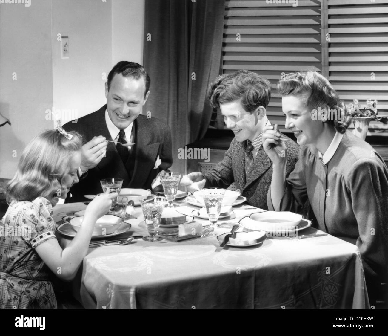 1930s 1940s HAPPY FAMILY EATING DINNER AT HOME - Stock Image