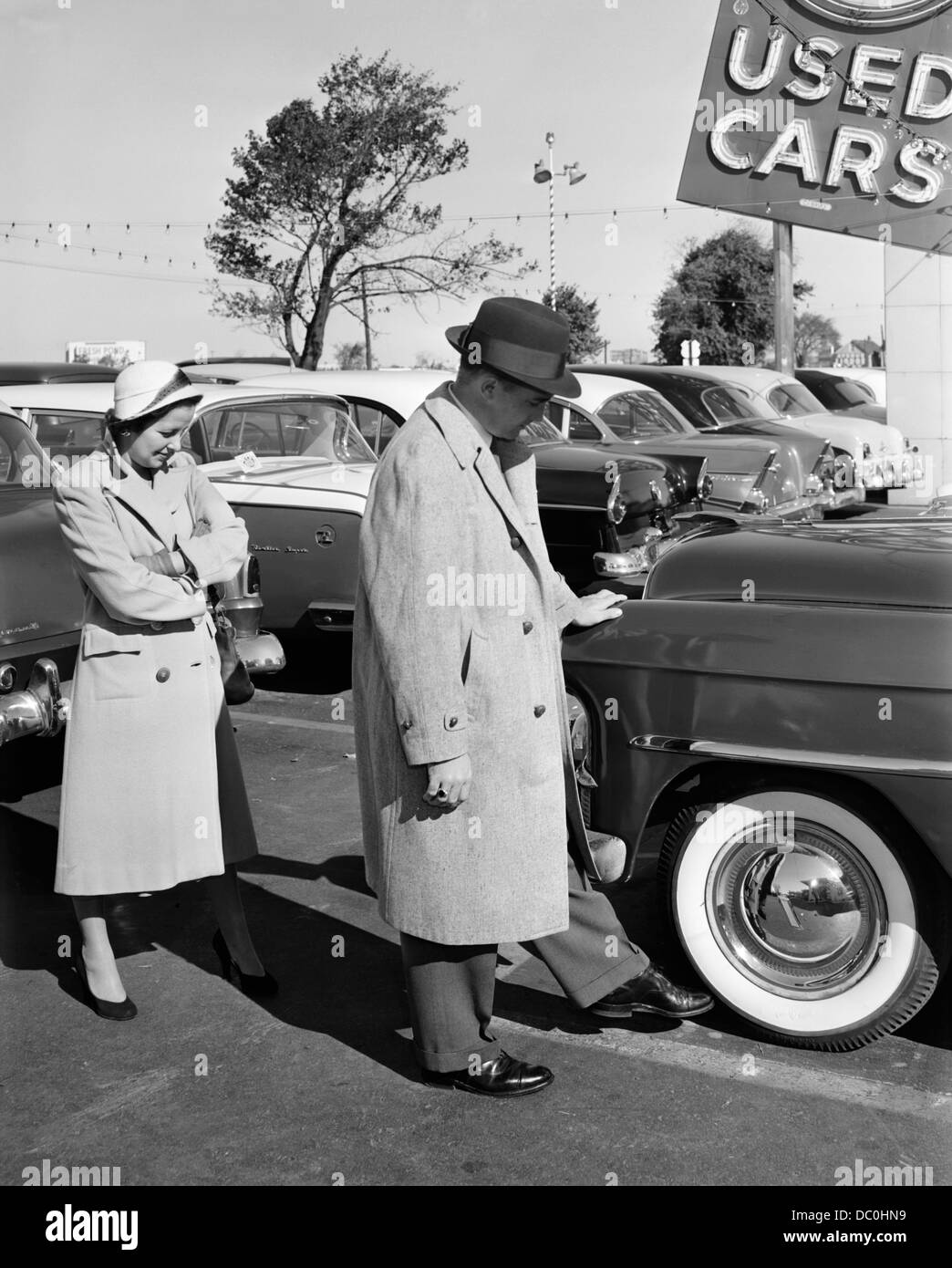 1950s COUPLE IN USED CAR LOT MAN KICKING TIRE