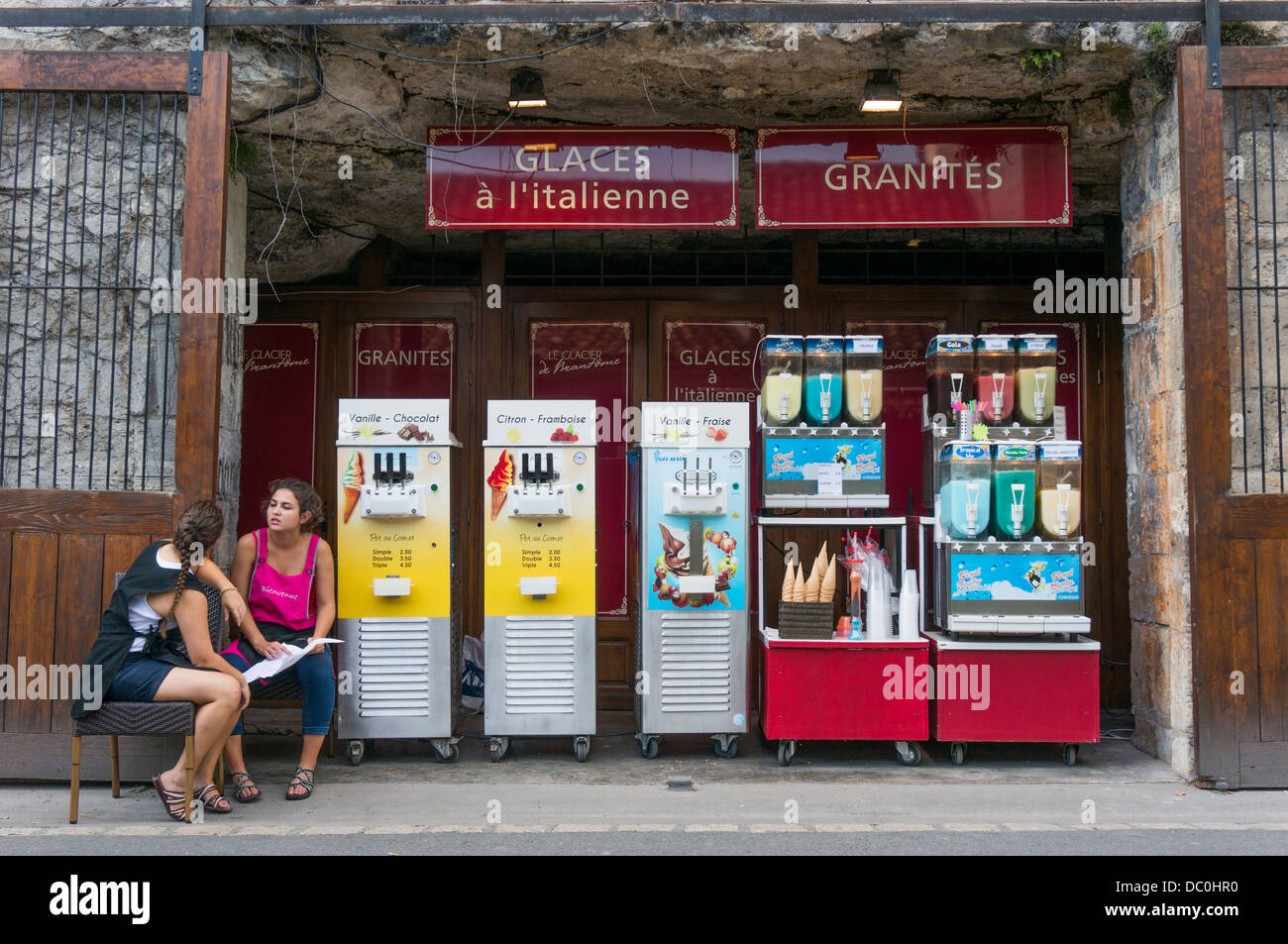 Two young women sitting waiting for tourists to sell ice cream, on a hot summer day in Brantôme, in the Dordogne - Stock Image