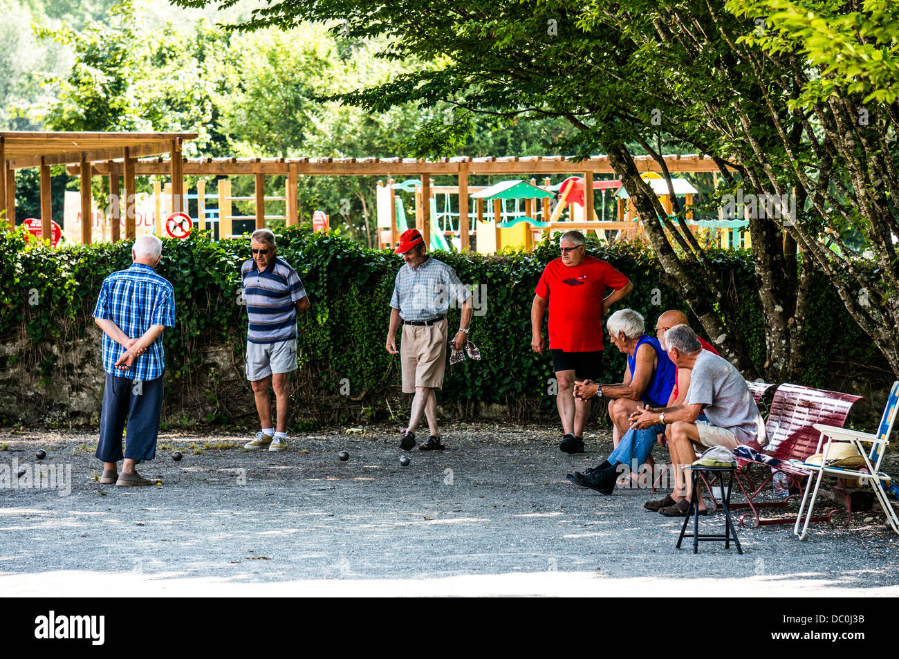 Old men playing a traditional game of boules (petanque) in a shaded area on a hot day, in Brantôme, in the - Stock Image