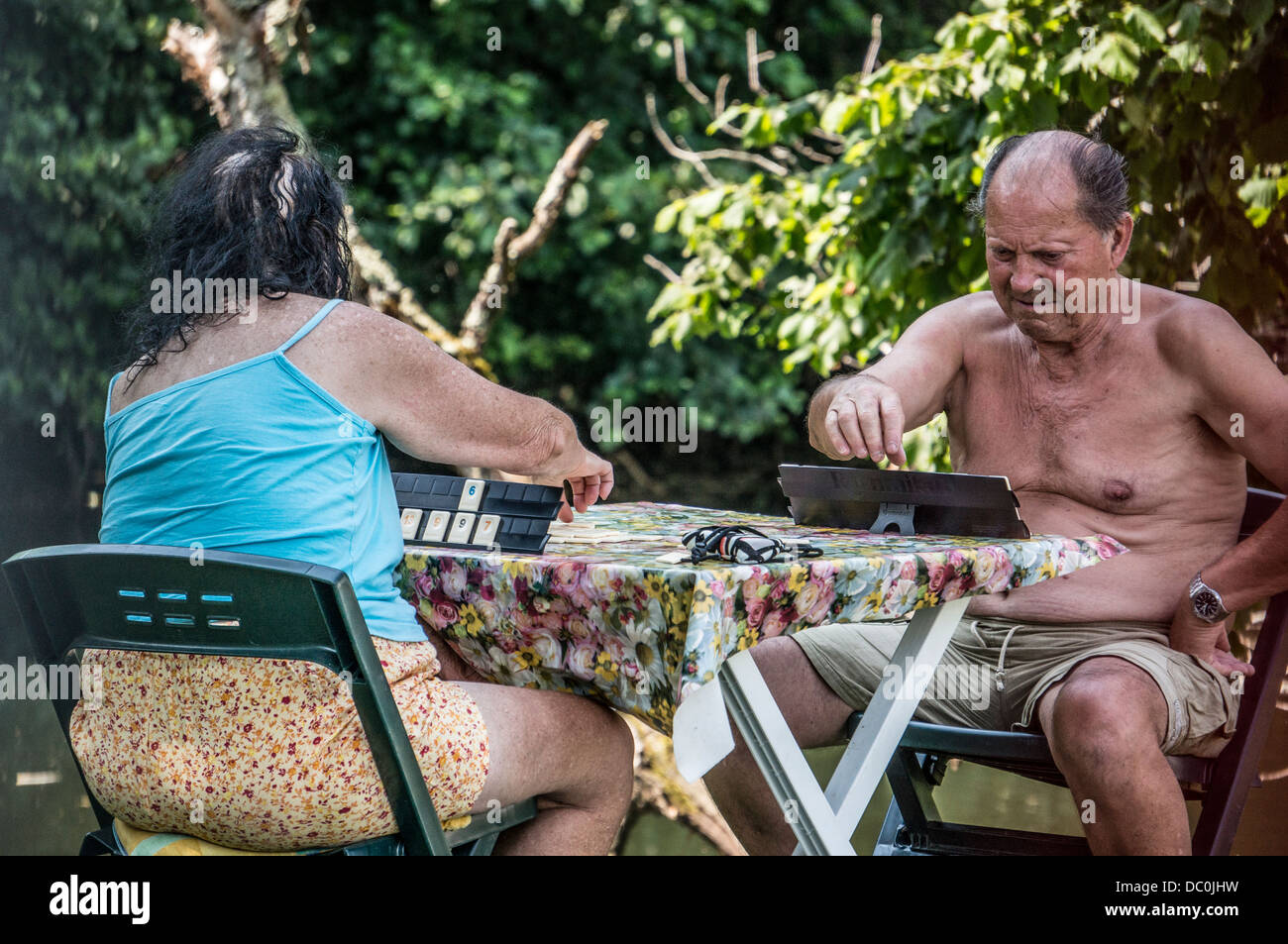 An old couple playing a board game, sitting at a table, outside in the hot weather, in Brantôme, the Dordogne - Stock Image