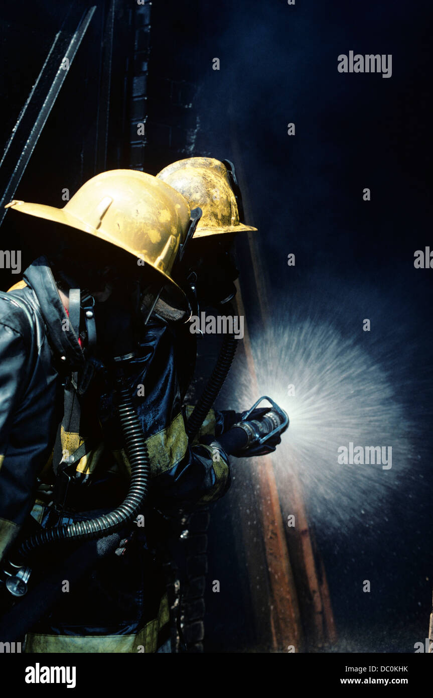 1970s TWO FIREFIGHTERS USE HOSE TO BATTLE FIRE - Stock Image