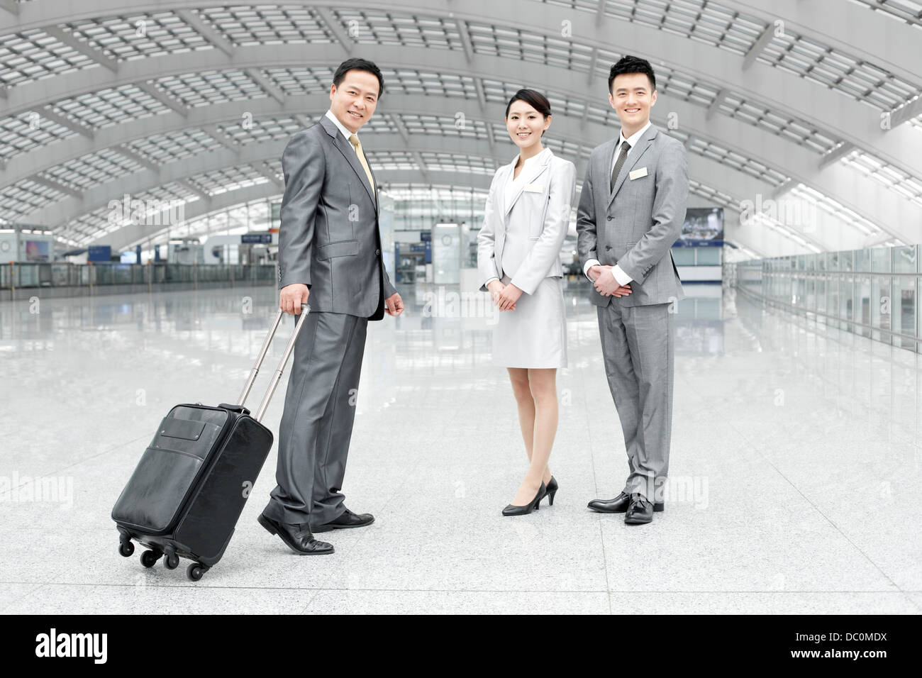 Young business partners with name tags greeting guest at the airport - Stock Image