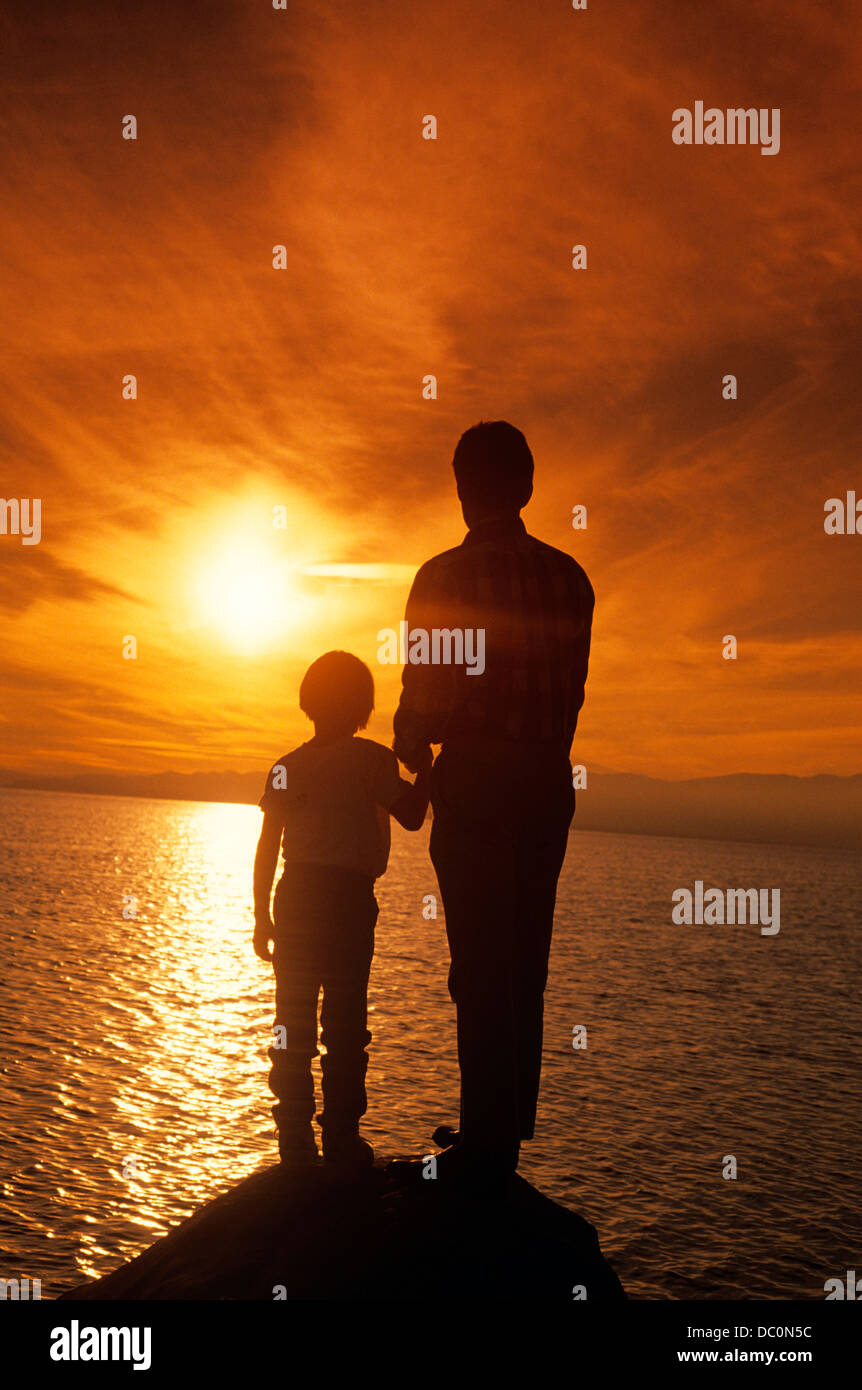 1990s SILHOUETTED FATHER AND SON WATCHING SUNSET OVER WATER Stock Photo