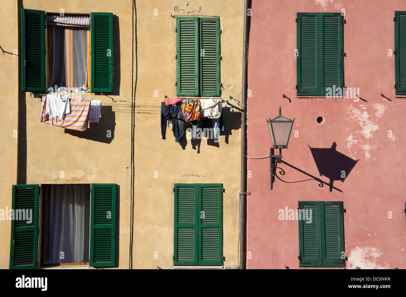 Neighbors hang clothes to dry in the sun on the facade of their houses - Stock Image