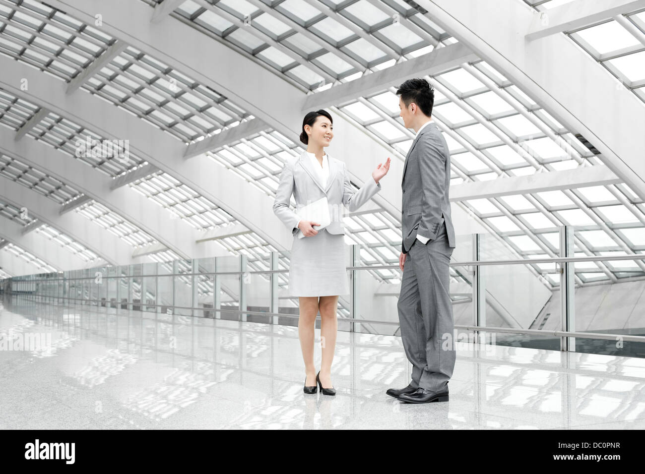 Young business partners talking at the airport - Stock Image