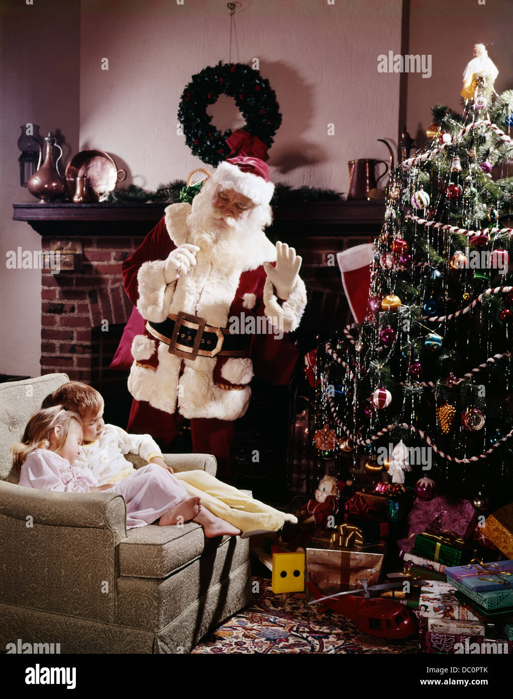 1960s 2 children boy girl sleep chair fireplace christmas eve santa waves hand tree gifts toys night before retro xmas - Children Christmas Pictures 2