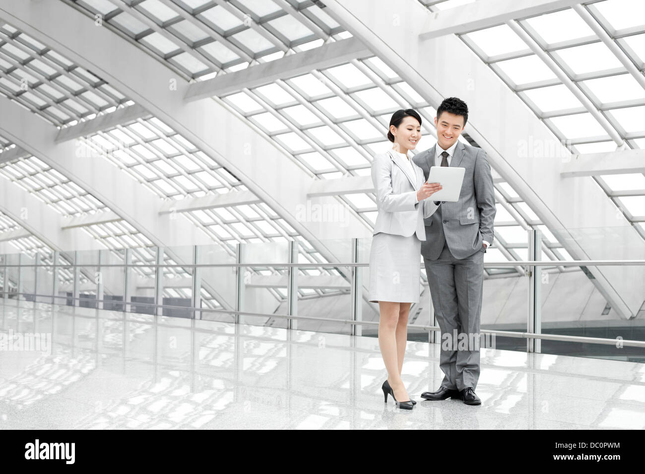 Young business partners with digital tablet at the airport - Stock Image