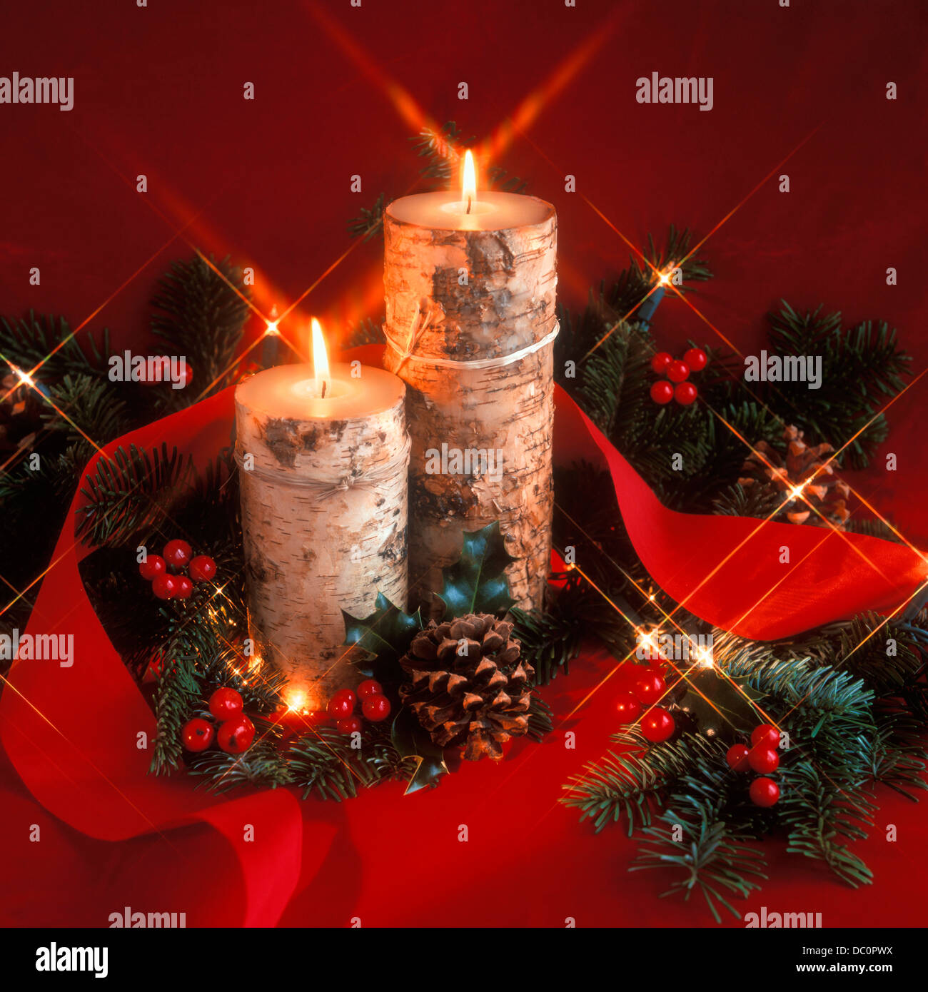 CHRISTMAS STILL LIFE WITH BARK COVERED CANDLE HOLDERS HOLLY BERRIES GREENS AND PINE CONES - Stock Image