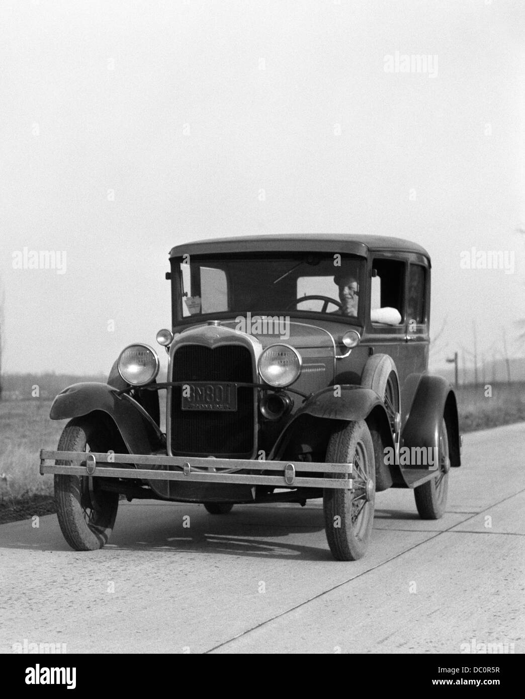 1930s YOUNG MAN DRIVING FORD MODEL A CAR OUTDOOR - Stock Image