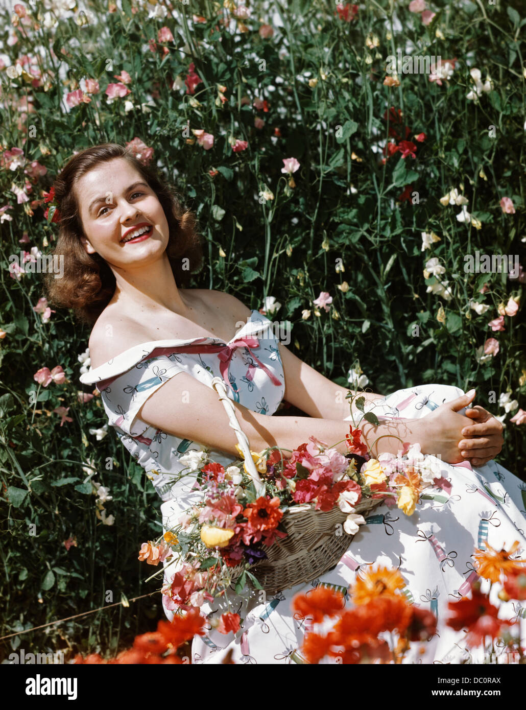 1950s SMILING WOMAN SITTING IN MEADOW HOLDING BASKET OF FLOWERS LOOKING AT CAMERA Stock Photo