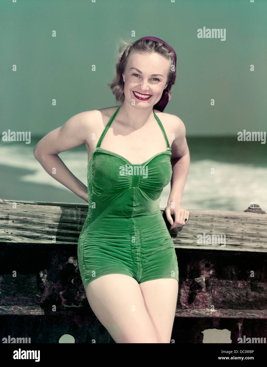 1940s PORTRAIT SMILING WOMAN WEARING GREEN VELVET BATHING SUIT POSING LEANING ON DIVING BOARD - Stock Image