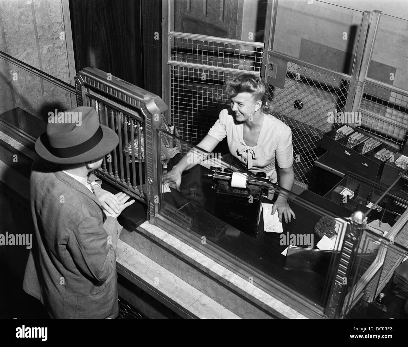1940s woman bank teller behind cage serving male customer. Black Bedroom Furniture Sets. Home Design Ideas