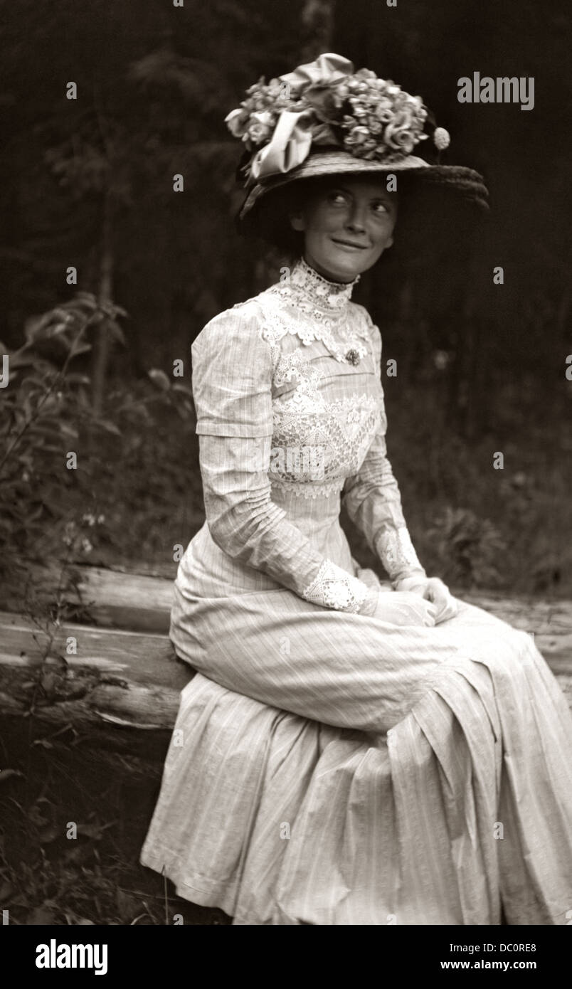 1900s 1910s TURN OF CENTURY BEAUTY ANONYMOUS WOMAN IN WHITE DRESS BIG HAT FLOWERS RIBBONS SUBTLE SMILE MICHIGAN - Stock Image