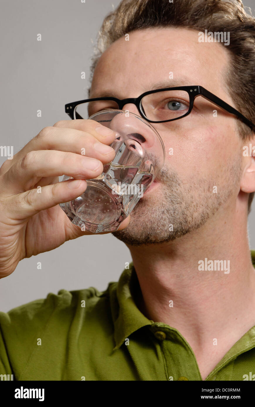 A man drinks a glass of water Stock Photo